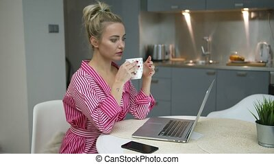 Woman drinking and using laptop