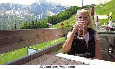 tourist girl drinking a draft beer on top Pradaschier park station of Churwalden town of Switzerland. Famous tourist resort for climbing activities and toboggan run in Grisons canton.