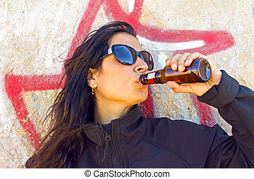 Woman drinking beer in front of a graffiti wall