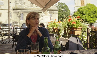 Woman drinking beer in open air caffee