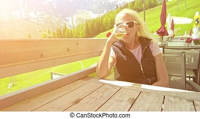 Girl at sunset drinking a draft beer on top Pradaschier park. Station of Churwalden town of Switzerland. Swiss tourist resort for climbing activities and toboggan run in Grisons canton.