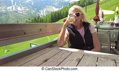 Woman drinking a draft beer on top Pradaschier park station of Churwalden town of Switzerland. Famous tourist resort for climbing activities and toboggan run in Grisons canton.