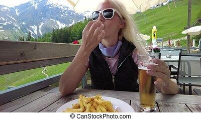 Woman drinking beer with French fries in Pradaschier park station of Churwalden in Switzerland. Swiss tourist resort for zip-line activities and toboggan run in Grisons canton.