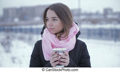 Woman drinking cappuccino coffee from a paper cup, in a...