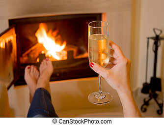 woman drinking Champange in front of a fire