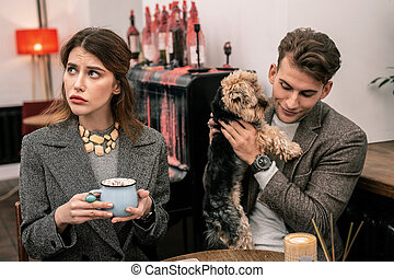 Woman drinking cocoa while man playing with a dog