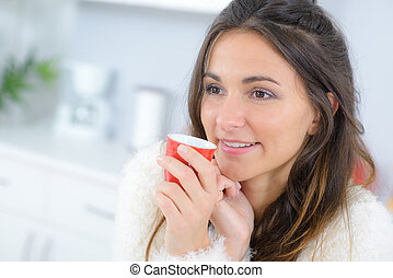 Woman drinking coffe in her kitchen