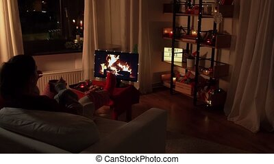 christmas, winter holidays and leisure concept - young woman drinking coffee or hot chocolate at cozy home with imitation of fireplace on tv screen