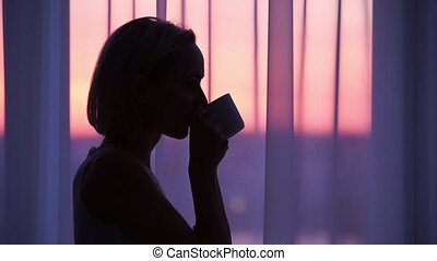 Woman drinking coffee at sunrise. silhouette of a woman