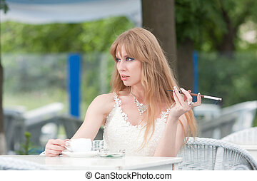 woman drinking coffee beautiful young woman with long hair drinking coffee and smoking in a cafe stock image csp17267969