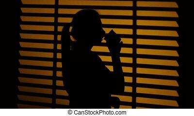 Woman drinking coffee from a cup. Silhouette. Close up