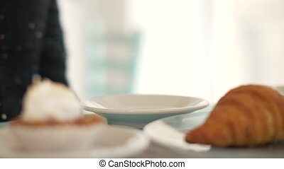 Woman drinking coffee from white cup at table in bakery cafe close up