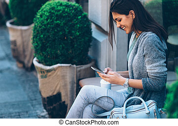 Woman drinking coffee in front of cafe