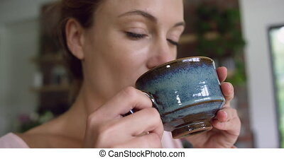 Woman drinking coffee in kitchen at comfortable home 4k