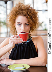 Woman drinking coffee in restaurant