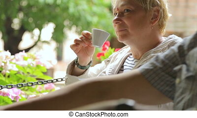 Woman drinking coffee in street cafe