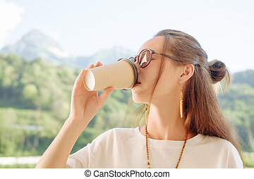 Woman drinking coffee in summer morning.