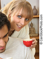 Woman drinking coffee next to husband