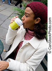 Woman Drinking Coffee - An young business woman takes a sip...
