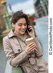 Woman Drinking Coffee Talking on Cell Phone, London, England