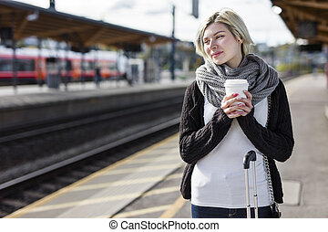 Woman drinking coffee while she waiting for the train