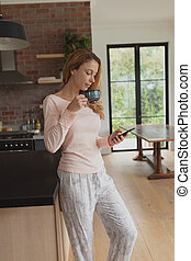 Woman drinking coffee while using mobile phone
