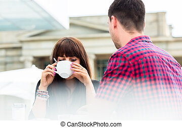 Woman drinking coffee with her friend