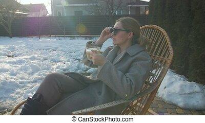Woman drinking coffee yard camera movement