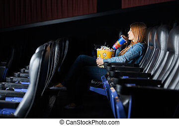 Woman Drinking Cola While Watching Movie At Theater