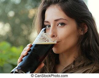 Woman drinking dark beer outdoor. Closeup portrait