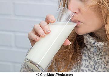woman drinking glass of milk in the foreground
