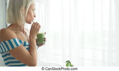 Woman drinking green vegetable smoothie at kitchen. Healthy eating lifestyle