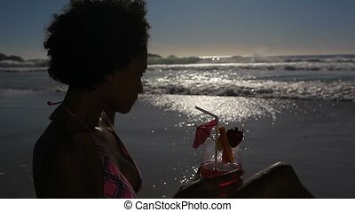 Woman drinking her cocktail with a straw on the beach