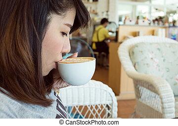 woman drinking hot coffee or tea in coffee cafe