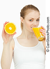 Woman drinking in a glass while presenting an orange