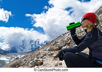 Woman drinking in mountains