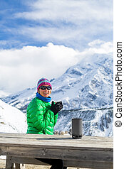 Woman drinking in winter mountain base camp