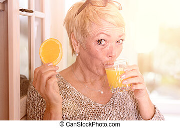 Woman Drinking Juice and Holding Orange Slice
