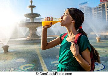 Woman drinking juice near the fountain