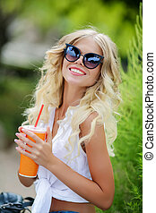 Woman drinking juice on a hot summer day.