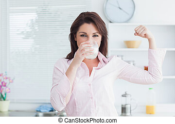 Woman drinking milk and flexing muscles - Portrait of young ...