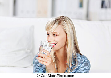 Smiling healthy woman drinking a large glass of bottled mineral water to quench her thirst
