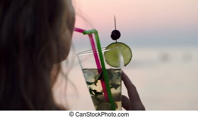 Woman drinking mojito with a straw - Close-up shot of a...