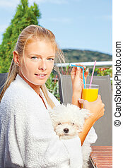 Woman drinking morning juice on terrace with her dog