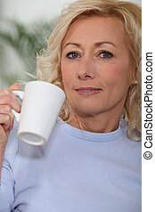 Woman drinking mug of coffee at home