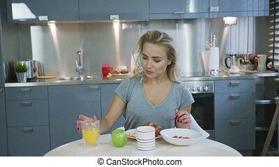Woman drinking orange juice for breakfast