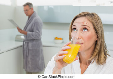 Woman drinking orange juice with man in background