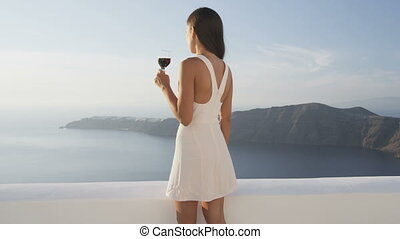 Young woman drinking red wine while standing at observation point. She is watching beautiful view of sea and mountains. Female in white sundress is on summer vacation. Video from Santorini, Greece.