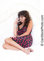 Woman Drinking Red Wine from a Glass in Bedroom