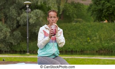 woman drinking smoothie after exercising in park - fitness,...